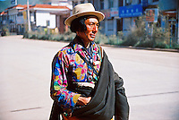 China, Guoluo, 2005. In the bright sun of midday, a Tibetan man surveys the empty streets of Guoluo.