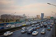 Traffic on motorway passes Olympics site of The Beijing National Stadium (Bird's Nest), China