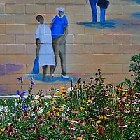 Summer flower garden and part of a brick wall mural depicting train travel near the Vienna Train Depot, Vienna, Virginia.