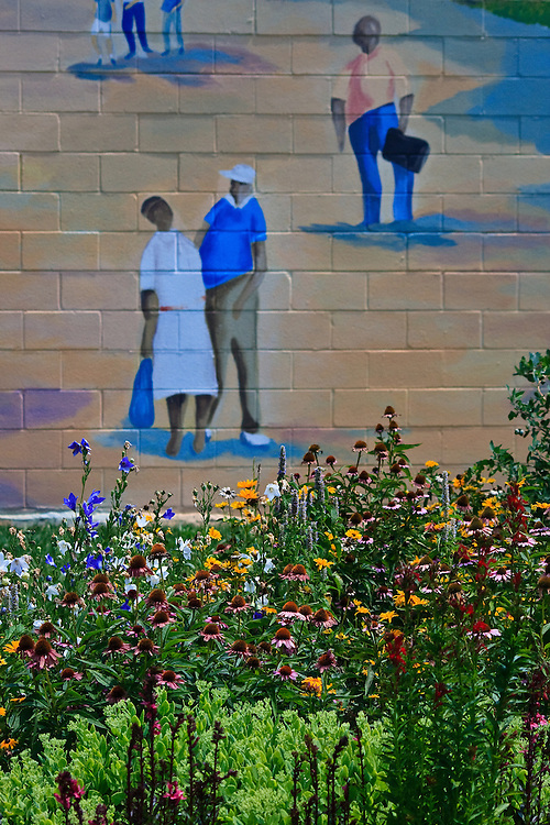 Summer flower garden and part of a brick wall mural depicting train travel near the Vienna Train Depot, Vienna, Virginia.