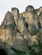 "Fantastic rock spires of Meteora rise above Kastraki, near Kalambaka, in central Greece, Europe. Meteora (which means ""suspended in the air"") is a complex of six Eastern Orthodox Christian monasteries built by medieval monks on natural rock pillars. The sandstone and conglomerate of Meteora were formed in the cone of a river delta estuary emerging into a sea about 60 million years ago, then later uplifted and eroded into pinnacles. The isolated monasteries of Meteora helped keep alive Greek Orthodox religious traditions and Hellenic culture during the turbulent Middle Ages and Ottoman Turk occupation of Greece (1453-1829). UNESCO honored Meteora as a World Heritage Site in 1988. Visit early in the morning and in the off season to avoid crowds."
