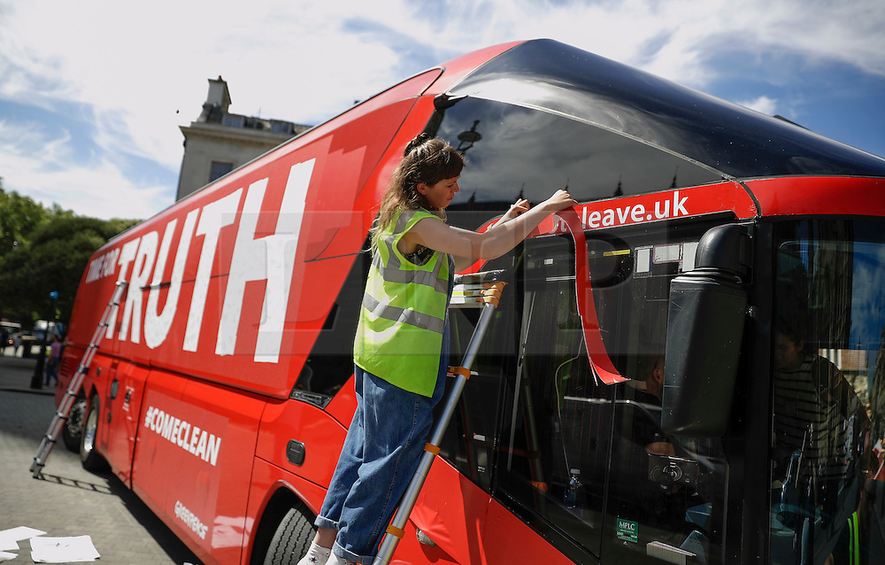 """© Licensed to London News Pictures. 18/07/2016. London, UK. The wording """"voteleave.uk"""" being covered up with tape. A bus used by the Leave campaign during the EU referendum, rebranded by Greenpeace outside the Houses of Parliament in London. The """"Brexit Bus"""" was previously covered in a slogan claiming that £350 million sent to the EU could be spent on the NHS.  Photo credit: Peter Macdiarmid/LNP"""
