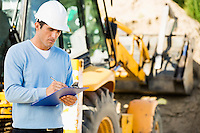 Male architect writing on clipboard against earthmover at construction site
