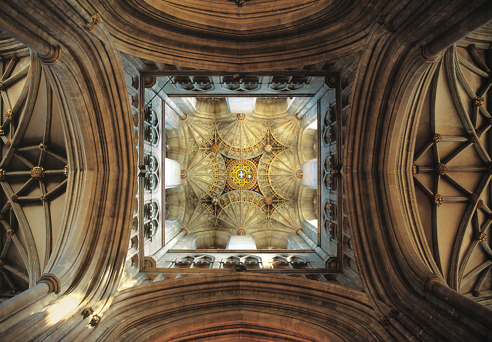 An upward view inside Canterbury Cathedral reveals the intricate ceiling design of Bell Harry Tower, in Canterbury, Kent, England.