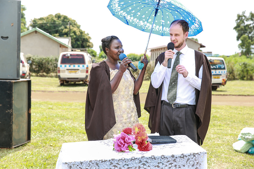 CAPTION: Relying on one of the instructors for local language support, World Renew volunteer Antony Sytsma delivers a speech during the TLT graduation in Kaberamaido. Andrew was trained by the Christian Reformed World Missions (CRWM) for this work. LOCATION: Kaberamaido, Kaberamaido District, Uganda. INDIVIDUAL(S) PHOTOGRAPHED: Unknown (left) and Antony Sytsma (right).