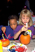 Friends painting pumpkins at Youth Express Halloween party age 6.  St Paul  Minnesota USA