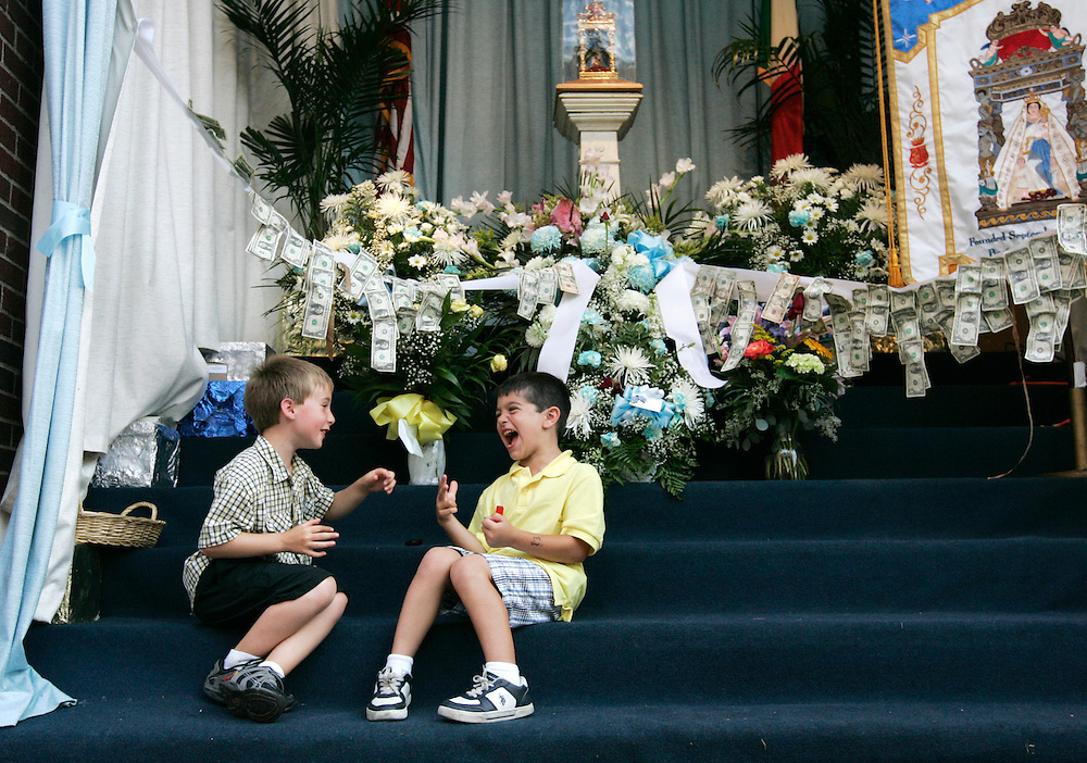 (Boston, MA - August 16, 2009) - Jake Dufresne (left), 7 of Stoughton, and Joshua Catallo, 6 of Medford, laugh as they play paper, rock and scissors at the feet of the statue of the Madonna del Soccorso outside the Fisherman's Club in Boston's North End. The club was decorated with money and flowers people had donated as part of the 99th Annual Fisherman's Festival. The money supports the club's various charitable acts. ..Herald photo by Will Nunnally