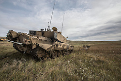 © Licensed to London News Pictures. 08/10/2014.  British Army Training Unit Suffield (BATUS), Canada. A Challenger 2 tank is recovered from thick clay as it makes it's way across a prairie in Canada.  Weighing 60 tonnes the vehicles can often become bogged down in the varied terrain.  <br /> <br /> BATUS has been home to the Army for the past 42 years .  It is the only place where all elements of the British Army train together for war.  The soldiers are put to test on everything from armoured vehicles to infantry tactics.        Photo credit : Alison Baskerville/LNP