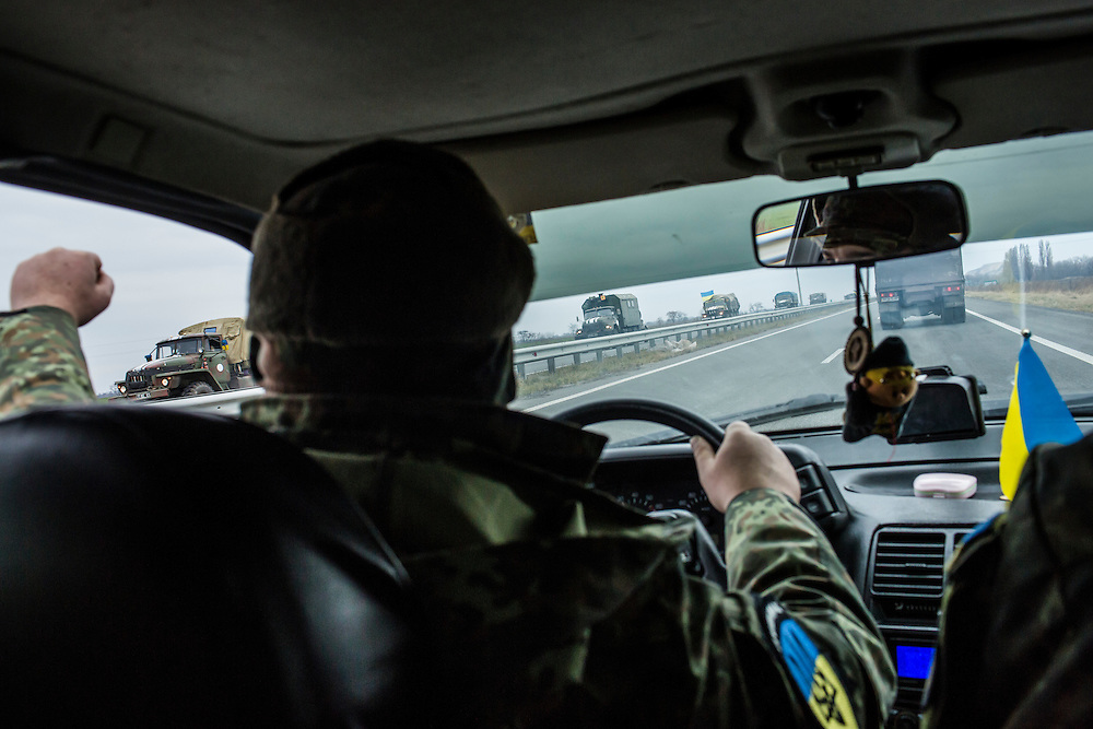 KARLIVKA, UKRAINE - NOVEMBER 17, 2014: A member of the Dnipro-1 brigade, a pro-Ukraine militia, puts his fist out the window of his car to salute passing Ukrainian army troops on a highway near Karlivka, Ukraine. CREDIT: Brendan Hoffman for The New York Times