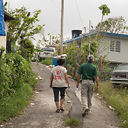 OCTOBER 18 - LARES, PUERTO RICO - <br /> Mercy Corps staffer Jasmine Avgerakis and Rafael Martinez Mu&ntilde;iz, of the GRALP (Grupo de Recuperation a Largo Plazo) walk up to a home in the Seburuquillo neighborhood in Lares doing field research on Puerto Rico's supply needs following the destructive path of hurricane Maria.<br /> (Photo by Angel Valentin for NPR)