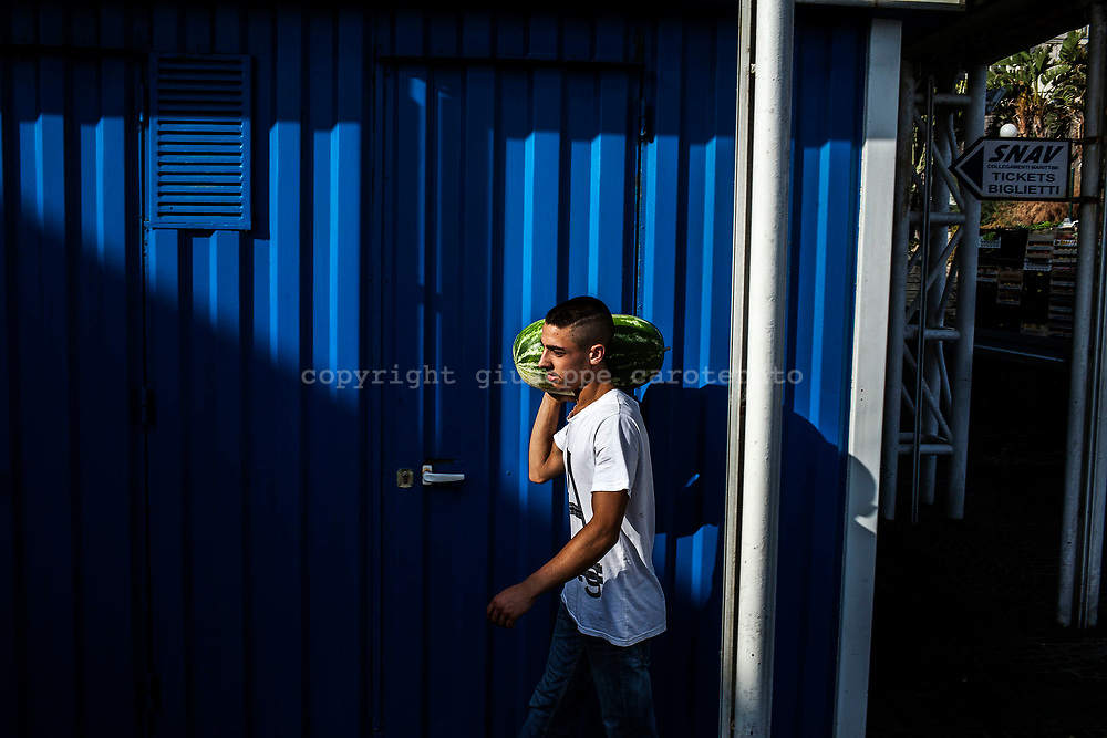 04 August 2017, Capri Italy - A young merchant with a melon on your shoulders during the morning near Marina Grande.