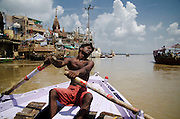 An oarsman rowing a tourist boat.<br />