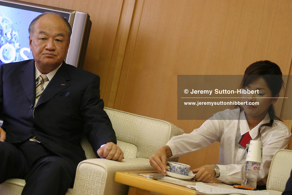 An employee positions a cup of tea for Katsuhiko Machida, President of Sharp, in Osaka, Japan, on Friday, Sept. 30th 2005. During interviews it is common for female assistants to enter the rooms silently , bringing refreshment drinks of green tea, coffee, or orange juice, to the company head and his guests.