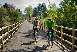 United States, Washington, Kirkland. Couple cycling along the Cross Kirkland Corridor, a former railroad line converted to a trail for walking and bicycling.