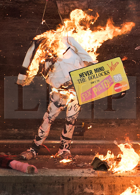 """© Licensed to London News Pictures. 26/11/2016. London, UK. A burning effigy of Jeremy Hunt holds up a Sex Pistols credit card mocking financial companies. Joe Corre (top right), the son of former Sex Pistol manager Malcolm McLaren and Vivienne Westwood burns his personal collection of Sex Pistols punk memorabilia. Earlier this week Joe Corre said that punk has become nothing more than a """"McDonald's brand ... owned by the state, establishment and corporations"""". His collection is estimated to be worth £5 million. Photo credit: Peter Macdiarmid/LNP"""