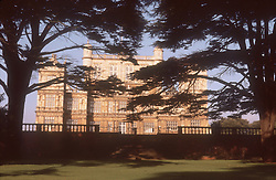 View of Wollaton Hall with cedar trees in foreground,