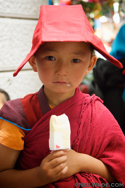 A very young novice Tibetan Buddhist monk eats some ice cream in Yushu, Tibet.