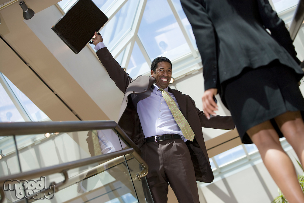 Excited business man holding briefcase in office building