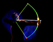 Profile of man with glowing bow and arrow.Black light