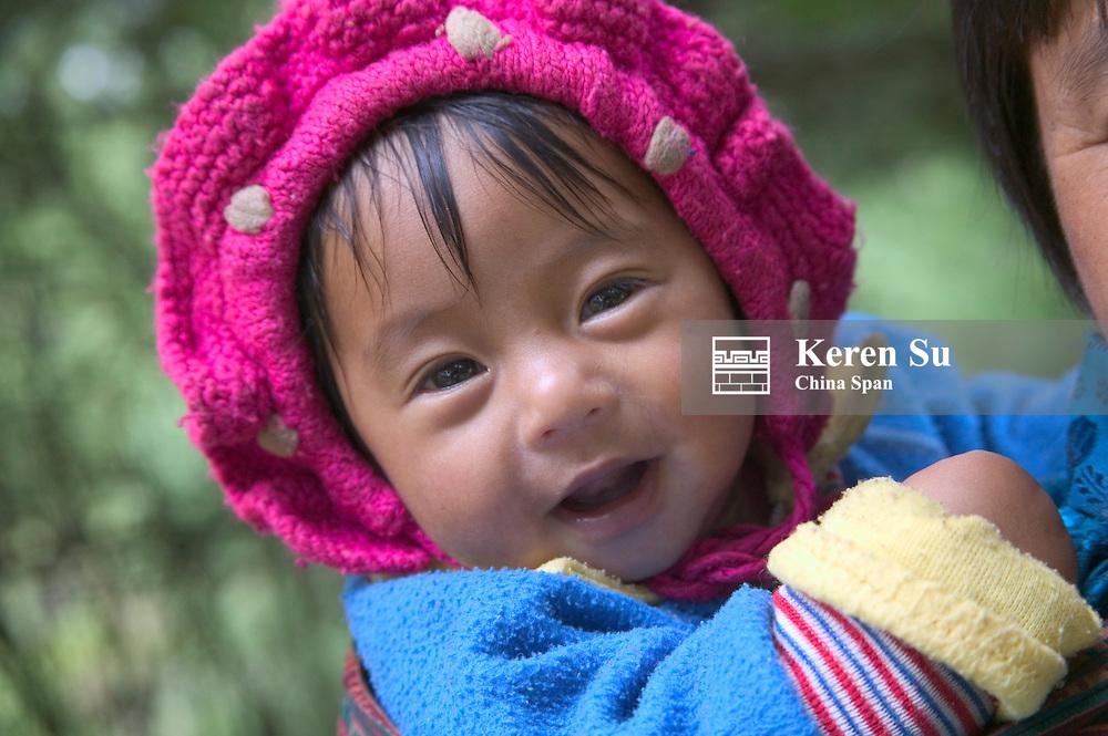 Portrait of a little girl on mother's back, Bhutan