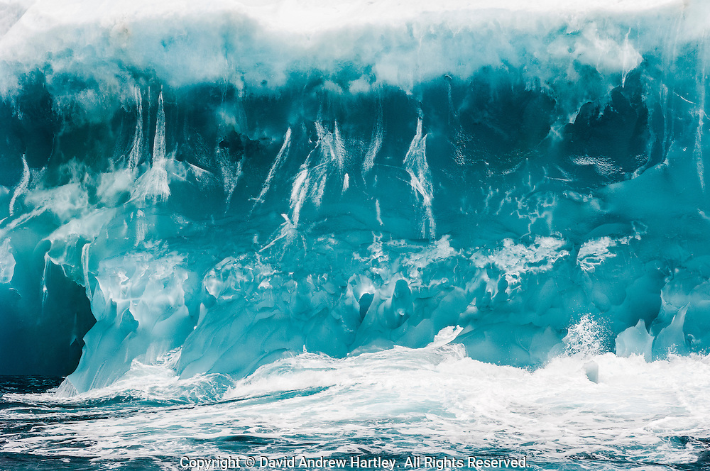Waves crash against a blue iceberg in the Scotia sea, South Atlantic Ocean