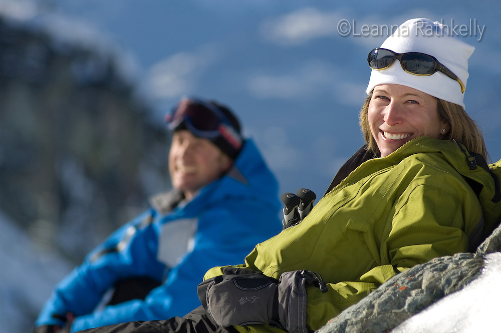 A couple takes a break from skiing on a sunny winter day