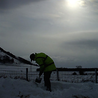 A farmer trying to dig his way into his farm just off the B9097 Crook of Devon to Scotlandwell road, after heavy snow drifts caused chaos on the roads in the Fife area<br />