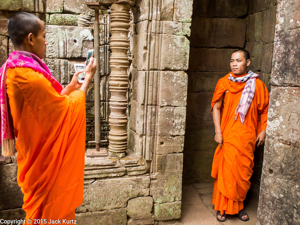 "14 MARCH 2105 - SIEM REAP, SIEM REAP, CAMBODIA: Buddhist monks walk around the Bayon, one of the temples in Angkor Thom, a part of the Angkor Wat complex. Bayon was built in 12th or 13th century CE. The area known as ""Angkor Wat"" is a sprawling collection of archeological ruins and temples. The area was developed by ancient Khmer (Cambodian) Kings starting as early as 1150 CE and renovated and expanded around 1180CE by Jayavarman VII. Angkor Wat is now considered the seventh wonder of the world and is Cambodia's most important tourist attraction.  PHOTO BY JACK KURTZ"