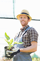 Portrait of happy gardener holding potted plant at greenhouse
