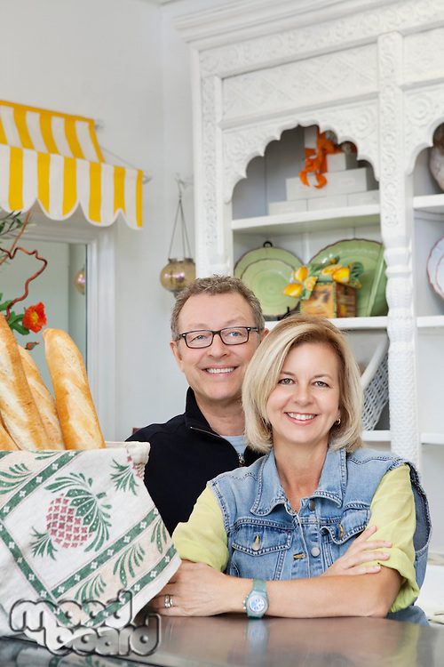 Portrait of happy mature couple standing at counter in cake shop