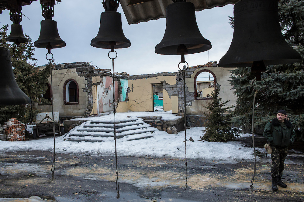 KIROVSKE, UKRAINE - JANUARY 31, 2015: A rebel fighter looks at the remains of a church which was destroyed when it was hit by a shell over the summer in Kirovske, Ukraine. Fighting in Ukraine has intensified over the last week, with rebels declaring the end of a September ceasefire. CREDIT: Brendan Hoffman for The New York Times