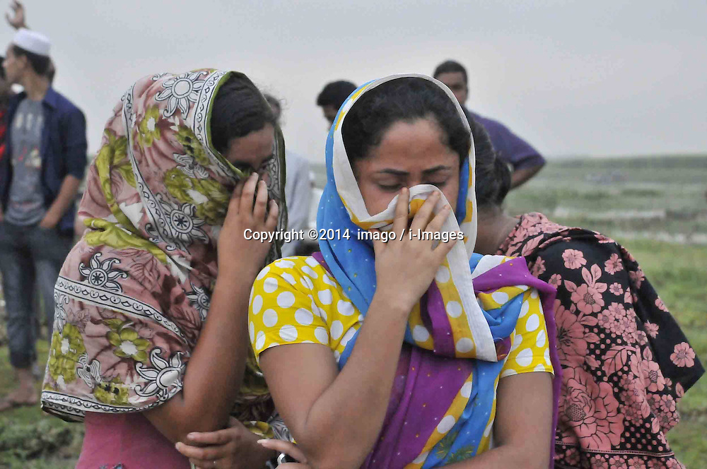 61530156<br /> Women stand at the side of a river after the ferry accident in Munshiganj district, Dhaka, Bangladesh, May 16, 2014. Bangladesh rescuers have dragged out 10 more bodies, raising the death toll to 22 in the ferry accident on river Meghna, after it sank in storm on Thursday afternoon,  Friday, 16th May 2014. Picture by  imago / i-Images<br /> UK ONLY