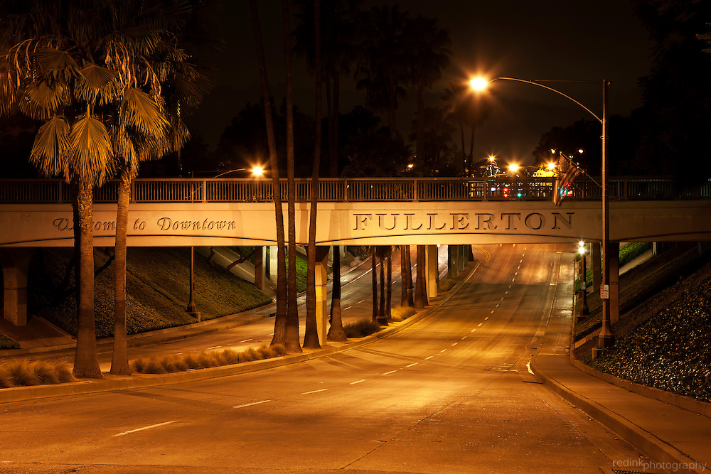 Welcome to Downtown Fullerton sign along train overpass as you enter the downtown Fullerton area along Harbor Blvd. Nightshot.