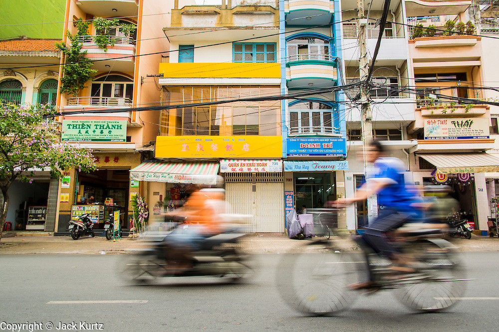 "12 APRIL 2012 - HO CHI MINH CITY, VIETNAM:  Traffic on a street in Cholon. Cholon is the Chinese-influenced section of Ho Chi Minh City (former Saigon). It is the largest ""Chinatown"" in Vietnam. Cholon consists of the western half of District 5 as well as several adjoining neighborhoods in District 6. The Vietnamese name Cholon literally means ""big"" (lon) ""market"" (cho). Incorporated in 1879 as a city 11 km from central Saigon. By the 1930s, it had expanded to the city limit of Saigon. On April 27, 1931, French colonial authorities merged the two cities to form Saigon-Cholon. In 1956, ""Cholon"" was dropped from the name and the city became known as Saigon. During the Vietnam War (called the American War by the Vietnamese), soldiers and deserters from the United States Army maintained a thriving black market in Cholon, trading in various American and especially U.S Army-issue items.         PHOTO BY JACK KURTZ"