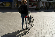 Amsterdam woman walking bicycle with a bent back wheel