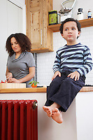 Boy (5-6) sitting on kitchen counter mother in backbround
