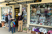 Tourists buying postcards from souvenirs and gifts shop in Burford in The Cotswolds, Oxfordshire, UK