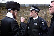 A member of the Neturei Karta demonstrates how he was punched to a community police officer as they were stopped trying to burn the Israeli flag in Stamford Hill, London during the festival of Purim. The Neturiei Karta oppose Zionism and believe that Jews are forbidden to have their own state until the coming of the Messiah.