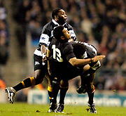 2004_'The Gartmore Challenge' - Barbarians_vs_New-Zealand..Casey Laulala is tackled by Lote Tuqiri and [left] Gcobani Bobo ..04.12.2004 Photo  Peter Spurrier. .email images@intersport-images.com...