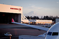 An image from Seatac airport of a Boeing 676 with a Northwest airlines hanger behind and Mount Rainier in the distance.