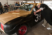 "The Full Nelson team driving a 1971 Saab 96 is placed under the scrutiny of Phil ""Judge Murilee Martin"" in the pit garage during the 24 Hours of Lemons race at New Hampshire Motor Speedway in Loudon.  (Karen Bobotas/for the Concord Monitor)"