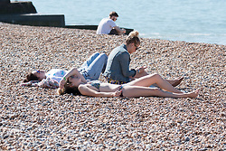 © Licensed to London News Pictures. 08/06/2014. Brighton, UK. A group of woman sunbathing on Brighton beach. with temperatures expected to be high Brighton is looking forward to another bumper Sunday for businesses.  Photo credit : Hugo Michiels/LNP