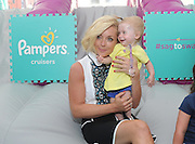 """Actress and mom Jane Krakowski plays with 10-month-old Rebecca Palumbo, of Italy, at the launch of the Pampers Cruisers #SagToSwag Tour in New York, Wednesday, Aug. 12, 2015.   In celebration of the new and improved Pampers Cruisers diapers, Pampers is going on a national tour to transform the nation's babies from """"sag to swag"""" one bottom at a time.  (Photo by Diane Bondareff/Invision for Pampers/AP Images)"""