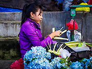 07 AUGUST 2017 - BEBANDEM, BALI, INDONESIA: A woman in the market in Bebandem, in far eastern Bali, makes small baskets used by Balinese in their daily offerings. The market is known for baskets, which are woven in the area. Bali's local markets are open on an every three day rotating schedule because venders travel from town to town. Before modern refrigeration and convenience stores became common place on Bali, markets were thriving community gatherings. Fewer people shop at markets now as more and more consumers go to convenience stores and more families have refrigerators.     PHOTO BY JACK KURTZ