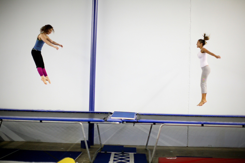 Kelly Shea, left, of University Park and Sheena Lee of Lewisville warm up on trampolines during Lone Star Circus' adult circus class in Farmers Branch, Texas.