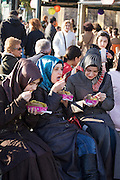 Istanbul. Ortako?y. Girls with headscarf having a typical snack: barbecued potato.