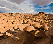 Admire fanciful hoodoos, mushroom shapes, and rock pinnacles in Goblin Valley State Park, in Emery County between the towns of Green River and Hanksville, in central Utah, USA. The Goblin rocks eroded from Entrada Sandstone, which is comprised of alternating layers of sandstone (cross-bedded by former tides), siltstone, and shale debris which were eroded from former highlands and redeposited in beds on a former tidal flat.