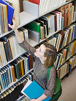 Young woman reaching for book in library view from above