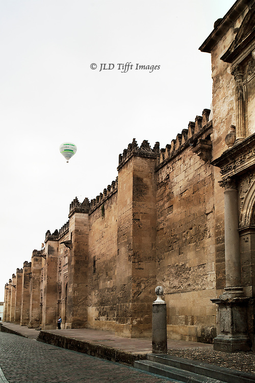 """Exterior view of the Cordoba Mezquita walls, above which a passenger balloon inscribed """"VICTORIA"""" floats."""