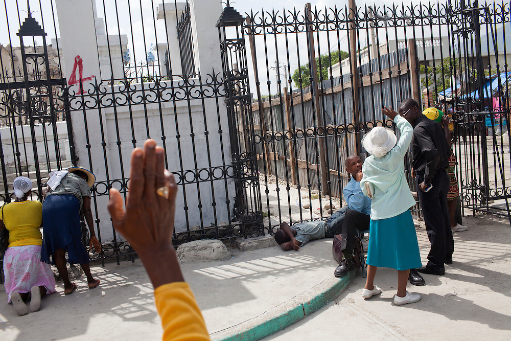 People pray in front of the destroyed national cathedral after a church service on July 11, 2010 in Port-au-Prince, Haiti.